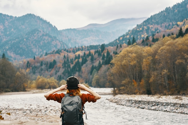 Vrouw rustend op de rivieroever in de bergen op natuurlandschap en modelrugzaktoerisme