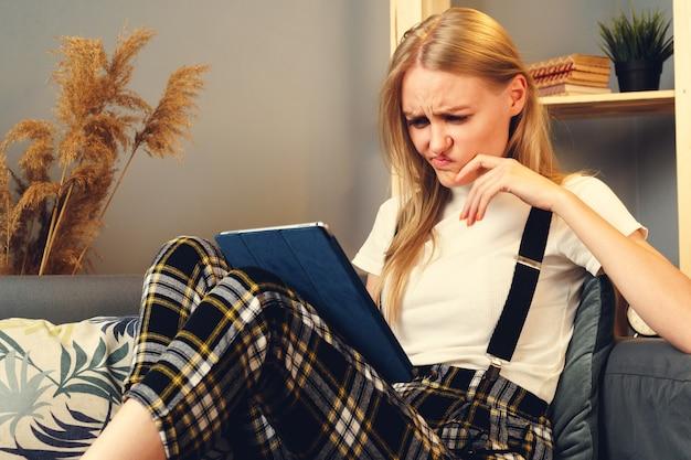 Vrouw 's nachts thuis surfen op internet met digitale tablet.