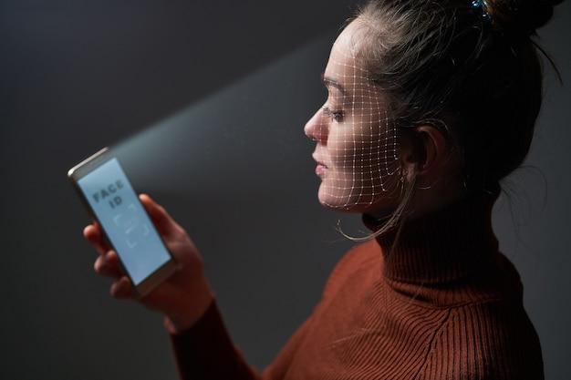 Vrouw scant gezicht met behulp van gezichtsherkenningssysteem op mobiele telefoon voor biometrische identificatie. toekomstige hi-tech technologie en gezicht-id