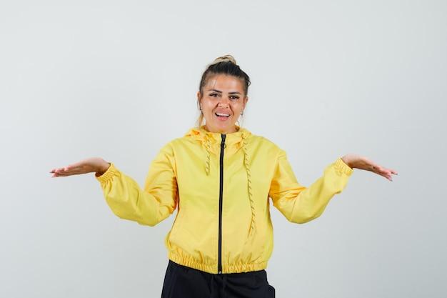 Vrouw schalen gebaar maken in sport pak en op zoek vrolijk, vooraanzicht.