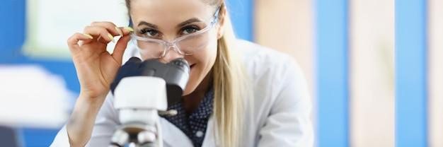Vrouw scheikundige in veiligheidsbril kijken door microscoop in laboratorium