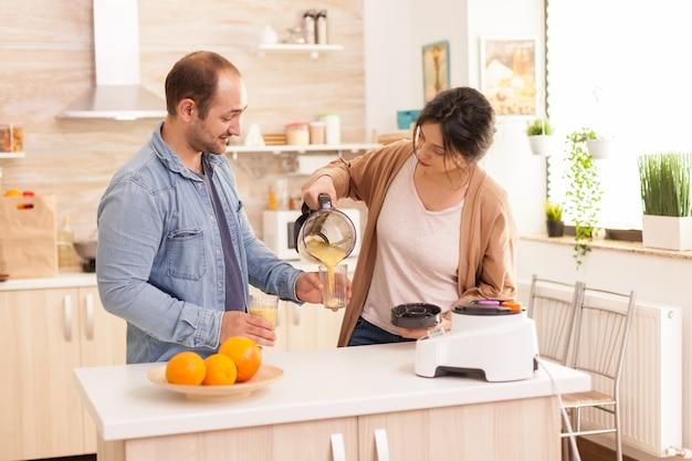 Vrouw schenkt smakelijke smoothie terwijl echtgenoot het glas vasthoudt. gezonde, zorgeloze en vrolijke levensstijl, dieet eten en ontbijt bereiden op een gezellige zonnige ochtend