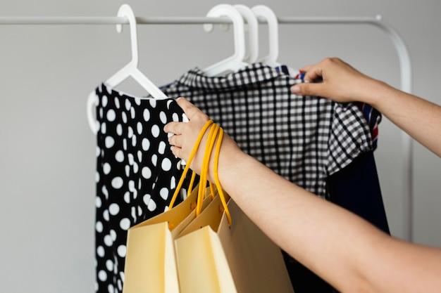 Vrouw schikken haar verkoop winkelen kleren op rek