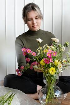 Vrouw schikt bloemen in een vaas