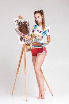 Vrouw schilder bevuild in kleurrijke verf tekent op canvas