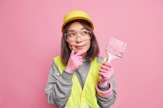 Vrouw schilder houdt hand op kin overweegt huisreparatie draagt beschermende bril helm en uniform houdt schilderborstel poses