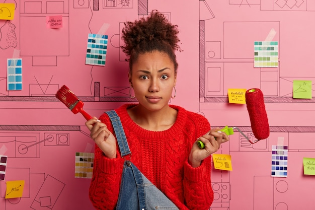 Vrouw schilder of decorateur houdt penseel en verfroller, verbetert huis, schildert appartement na verhuizing, bezig met huis renovatie, vormt tegen ontwerpschets. schilderen en herinrichting.