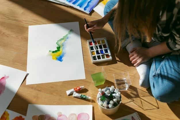 Vrouw schilder zittend op de vloer