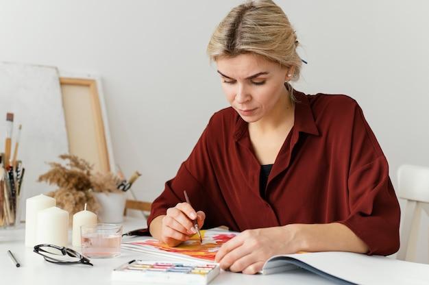 Vrouw schilderen met aquarellen op papier