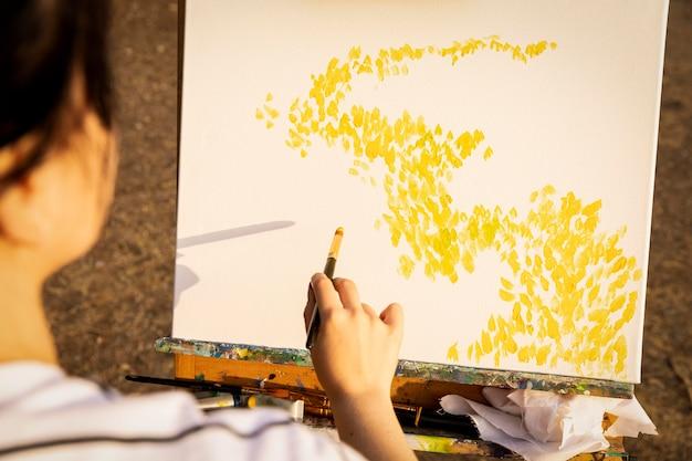 Vrouw schilderen op canvas buiten in de natuur