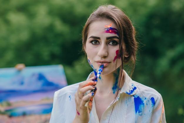 Vrouw schilderij een mujer pintándose un labio de azul con un pincelblue lip met een penseel