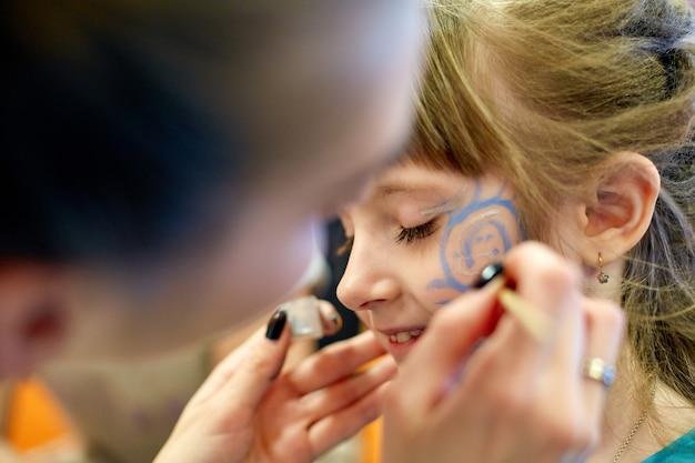 Vrouw schilderij gezicht van kind buitenshuis. baby schminken