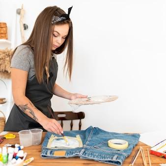 Vrouw schilderij korte broek middellange schot