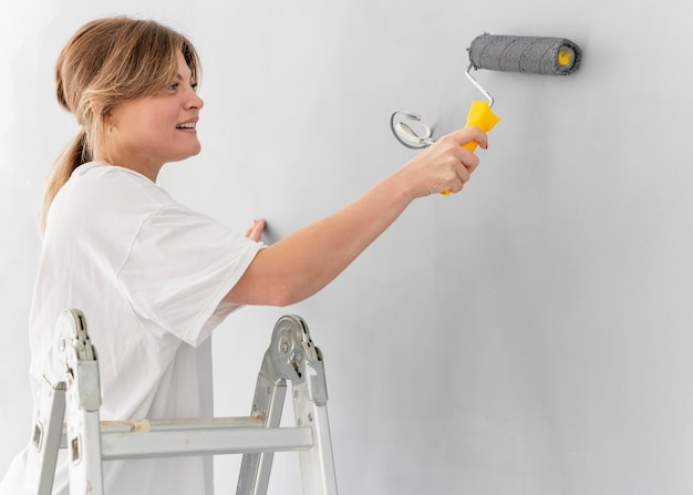 Vrouw schilderij muur met roller