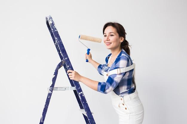 Vrouw schildert de muur tijdens herinrichting.