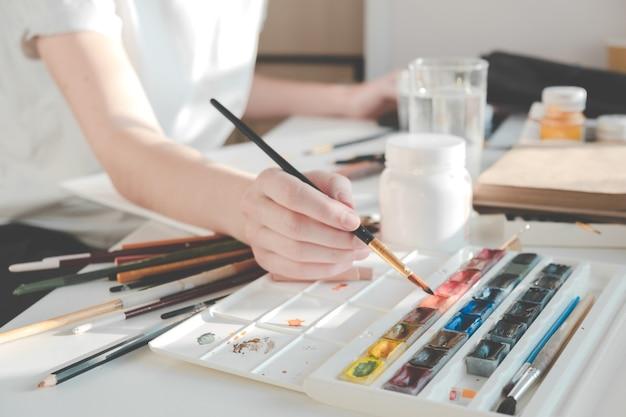 Vrouw schildert een afbeelding met een penseel. thuis leren tekenen.