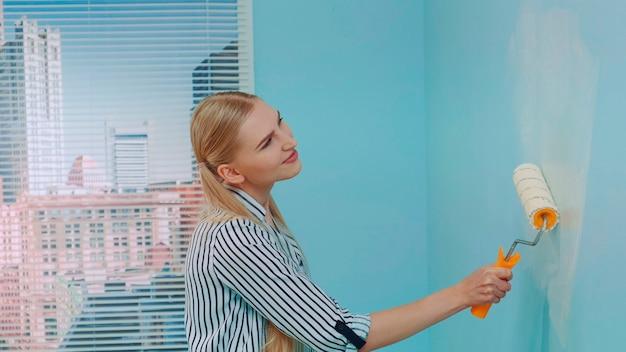 Vrouw schildert een muur op kantoor
