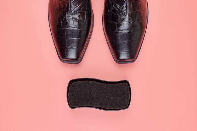 Vrouw schoenen met poetsmiddel spons, kopie ruimte, roze achtergrond. schoenverzorging of uitverkoop concept.