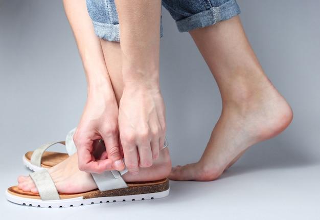 Vrouw schoenen stijlvolle lederen sandalen op haar voet op wit
