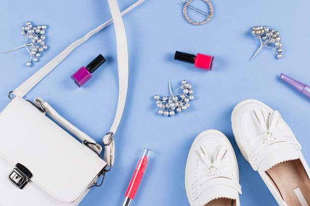 Vrouw schoenen, tas en cosmetica plat leggen. witte accessoires op blauw