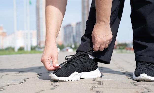 Vrouw schoenveters vastmaken aan haar snickers buitenshuis