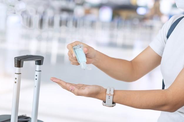 Vrouw schone hand door alcohol gel ontsmettingsmiddel na handvat bagage tas in luchthaven