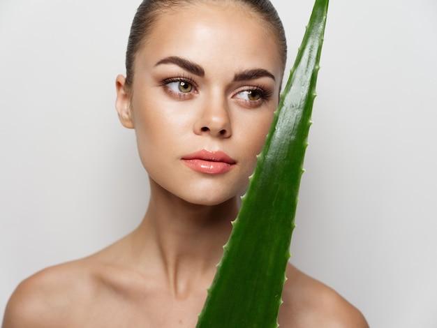 Vrouw schone huid groene lommerrijke blote schouders licht bijgesneden weergave