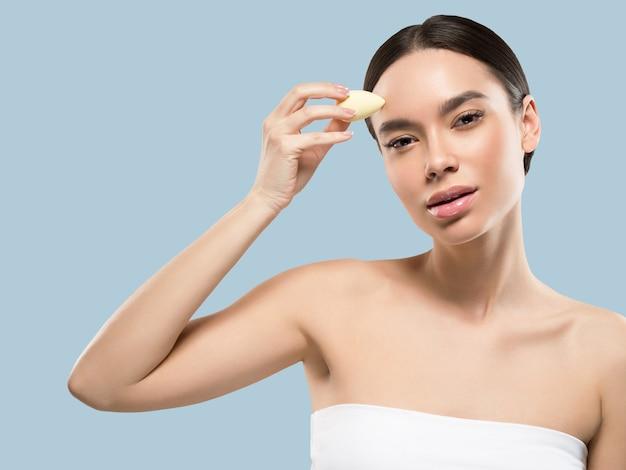 Vrouw schone huid met spons schoonheid gezonde huid schoonheid. kleur achtergrond. blauw