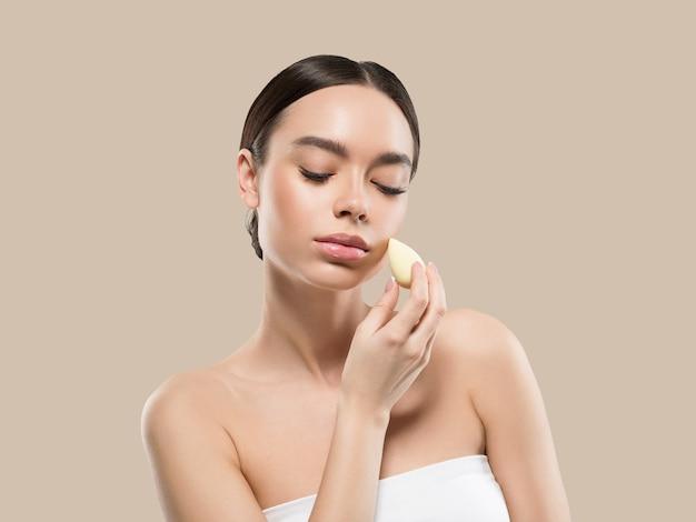Vrouw schone huid met spons schoonheid gezonde huid schoonheid. kleur achtergrond. bruin