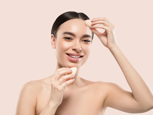 Vrouw schone huid met spons schoonheid gezonde huid schoonheid. kleur achtergrond. roze