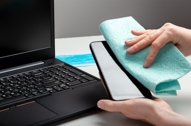 Vrouw schone smartphoon werkruimte. desinfectie telefoon en laptop toetsenbord door alcohol ontsmettingsmiddel. vrouw reiniging werkplek bureau bureau oppervlakken. nieuwe normale covid 19 coronavirushygiëne.