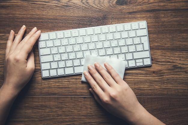 Vrouw schoon toetsenbord in servet op het bureau