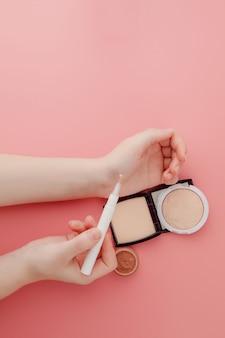 Vrouw schoonheid blogger handen met fles en buis spa professionele hi-end cosmetica op roze oppervlak, minimalisme concept, warme gezellige tinten en copyspace
