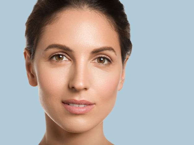 Vrouw schoonheid gezicht gezonde huid natuurlijk schoon fris gezicht. close-up bekijken. kleur achtergrond. blauw