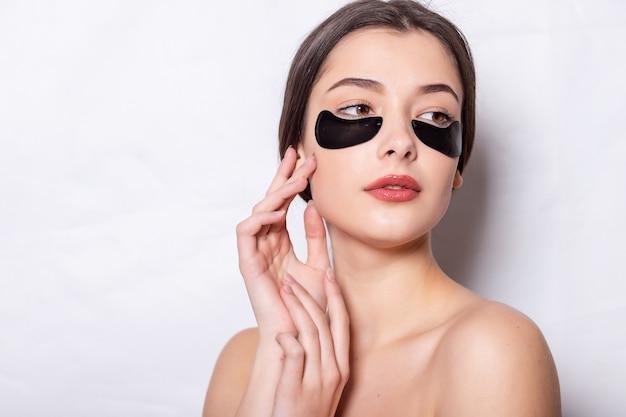 Vrouw schoonheid gezicht met masker onder de ogen. mooi meisje met natuurlijke make-up en zwarte hydrogel ooglapjes op de gezichtshuid. hoge resolutie
