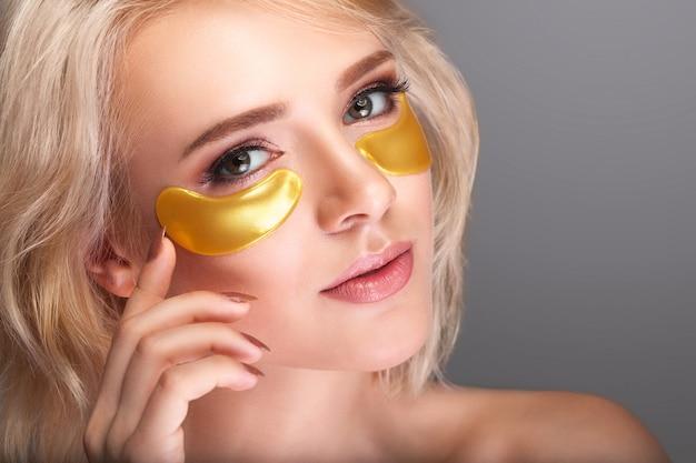 Vrouw schoonheid gezicht met masker onder ogen.