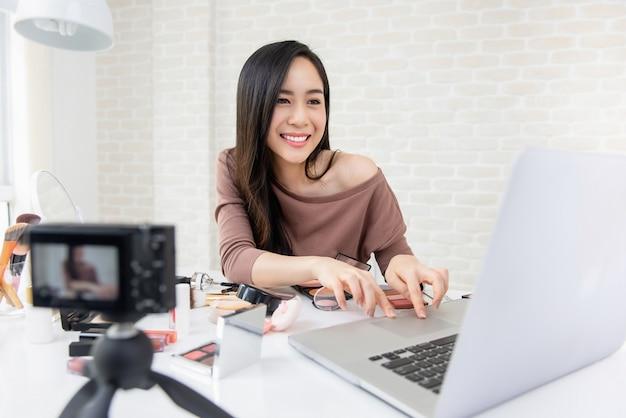 Vrouw schoonheid vlogger cheking feedback van doelgroepen uit sociale media live-uitzendingen
