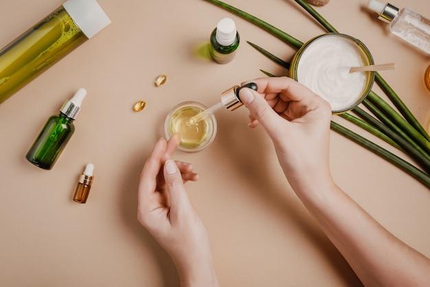 Vrouw schoonheidsspecialist cosmetica testen. natuurlijke biologische cosmetica. serum haarmasker. plat lag pastel