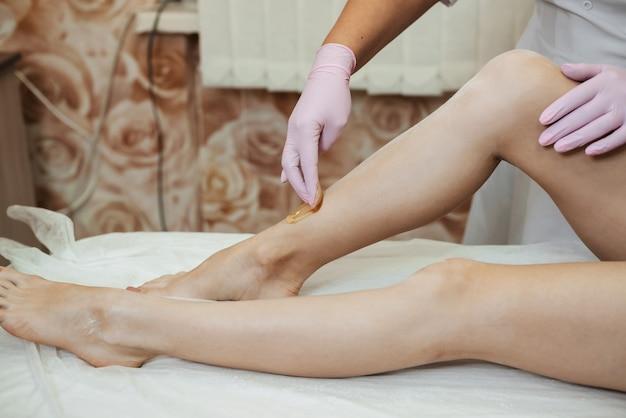 Vrouw schoonheidsspecialiste in de procedure van het verwijderen van haar op de benen van een meisje met suiker ontharing