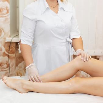 Vrouw schoonheidsspecialiste naast de gladde benen van het meisje klanten na behandeling ontharing