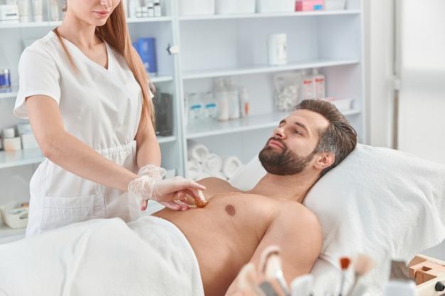 Vrouw schoonheidsspecialiste ontharingshars op de borst van jonge man voor ontharing. ontharen met was.