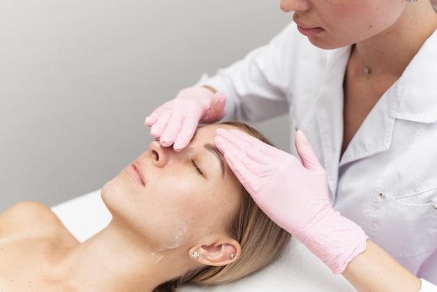 Vrouw schoonheidsspecialiste reinigt en hydrateert de huid van de patiënt in de spa salon.