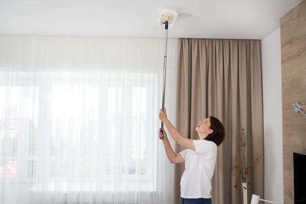 Vrouw schoonmaak plafond met een zwabber. huisvrouw schoonmaak woonkamer