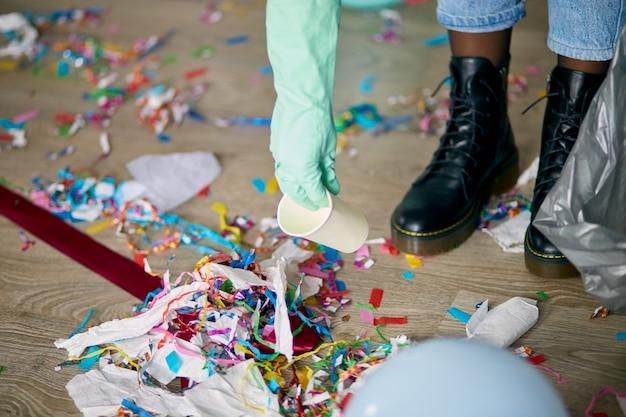 Vrouw schoonmaak puinhoop van vloer in kamer afterparty, verwijdert vuilnis van de vloer, wegwerpbekers in een zak, ochtend na feestviering, huishoudelijk werk, schoonmaakservice