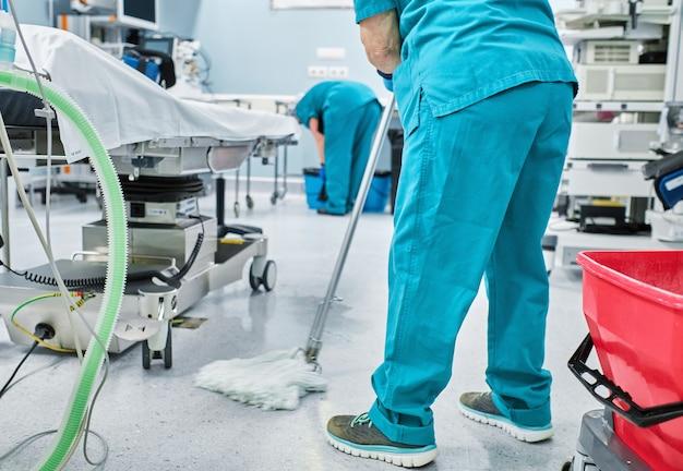 Vrouw schoonmaakpersoneel dweilt de vloer van een operatiekamer van een ziekenhuis