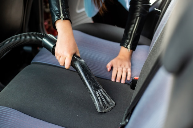 Vrouw schoonmaken, stofzuigen interieur van de auto door stofzuiger, transportconcept