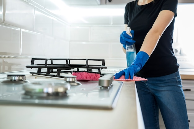 Vrouw schoonmaken van roestvrij staal gas oppervlak in de keuken met rubberen handschoenen.