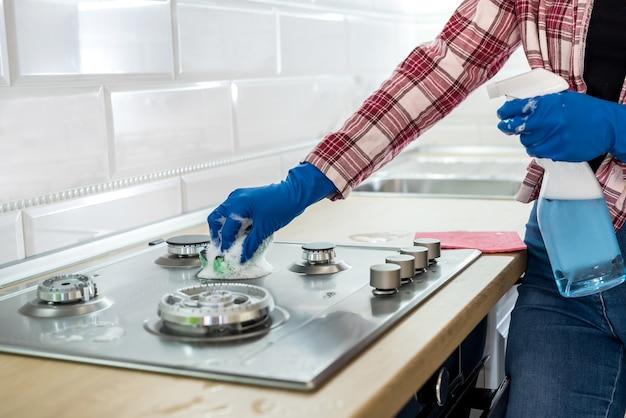 Vrouw schoonmaken van roestvrij staal gasoppervlak in de keuken met rubberen handschoenen.