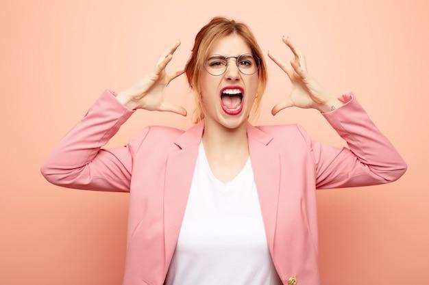 Vrouw schreeuwen met handen omhoog in de lucht, woedend, gefrustreerd, gestrest en boos voelen