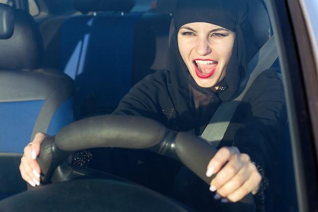 Vrouw schreeuwende liedjes zingen tijdens het besturen van een auto.,